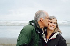 An old man is kissing his wife; they have become dependent on each other.