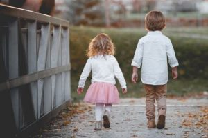A boy brings his little sister to play in the park when their parents are busy.